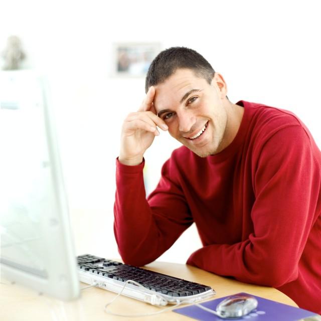 Young Man Sitting at a Computer