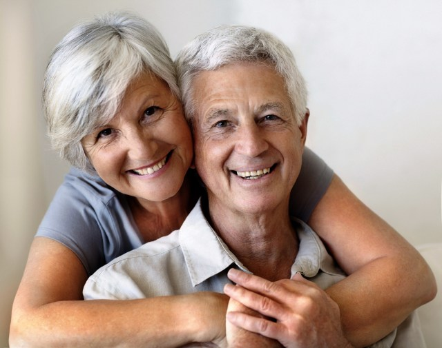 Portrait of a smiling senior couple embracing while sitting at home