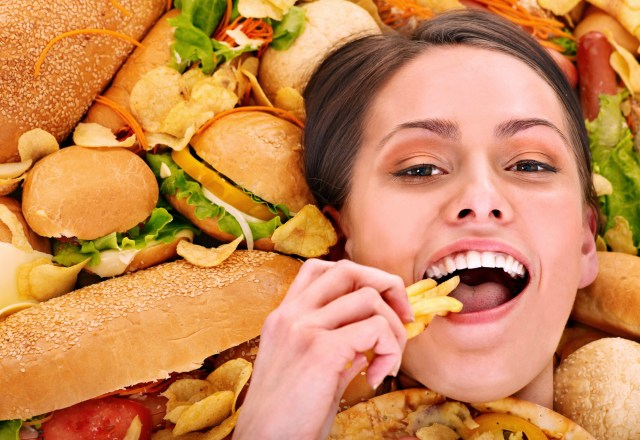 Thin woman holding hamburger.
