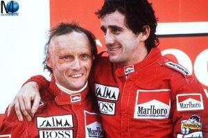 Der österreichische Formel-1-Rennfahrer Niki Lauda (l) mit seinem Teamkollegen, dem Franzosen Alain Prost, am 21.10 1984 nach seinem Sieg beim Grand Prix im portugiesischen Estoril. Das Formel-1 Finale im portugiesischen Estoril hätte spannender nicht sein können: Erst in den letzten Runden sicherte sich Niki Lauda durch den zweiten Platz hinter seinem Teamgefährten Alain Prost den Sieg in der Gesamtwertung und somit den WM-Titel 1984.